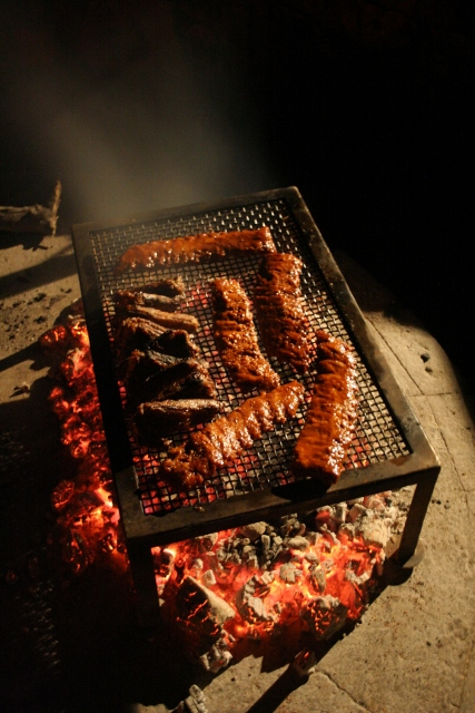 Ribs and lamb chops being cooked over an outdoor boma fire