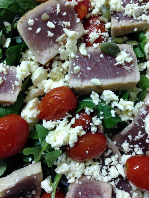 Seared tuna pieces with feta and cooked baby tomato's in a green salad
